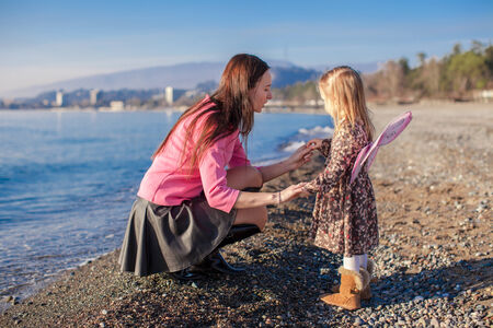 Little girl with mom having fun on the beach in a winter day photo