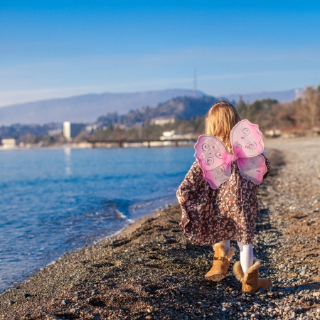 beach butterfly: Adorable little girl with butterfly wings running along the beach in a winter sunny day