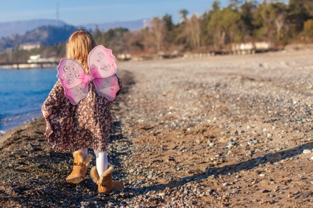 beach butterfly: Attractive little girl on the beach in a suit with butterfly wings