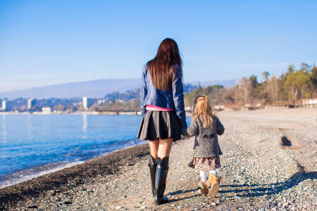Little girl and her mother walking on the beach in winter sunny day photo