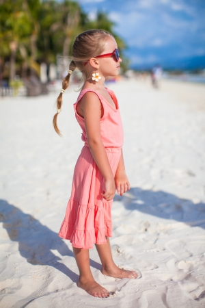 Adorable little girl on tropical beach vacation photo