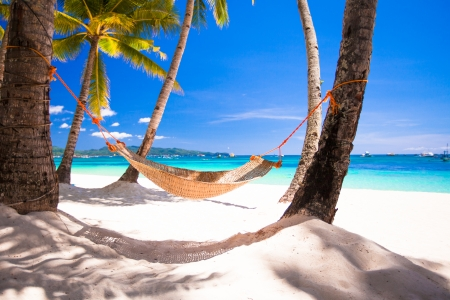 View of cozy straw hammock on the tropical white beach photo