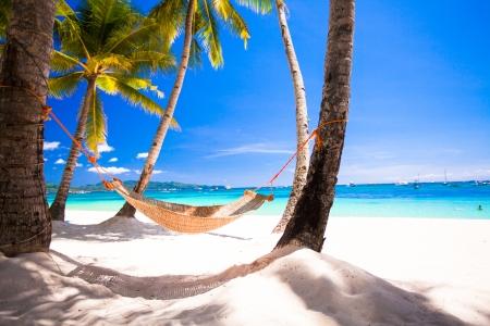 熱帯白いビーチで居心地の良いわらハンモックのビュー