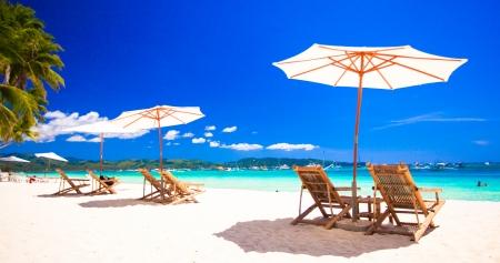 Beach chairs on exotic tropical white sandy beach photo