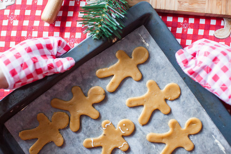Raw gingerbread men with glaze on a baking sheet photo