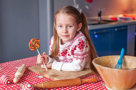 Little girl with candy in hand will prepare Christmas cakes photo