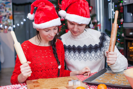 Happy family in Santa hats baking Christmas gingerbread cookies together photo