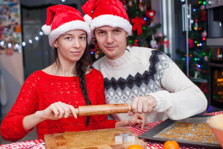 Young happy couple baking Christmas cakes photo