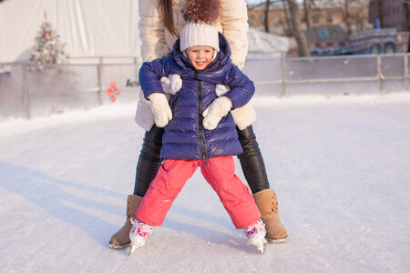 ice skates: Little adorable girl with her mom learning to skate