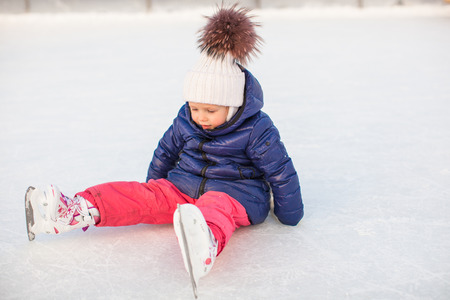 speed skating: Little adorable girl sitting on the ice with skates after the fall