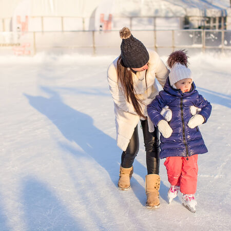 iceskating: Happy excited little girl and her young mother learning ice-skating