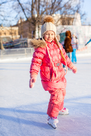 Adorable little girl enjoys skating at the ice-rink photo