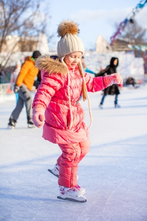 Charming little girl enjoys skating at the ice-rink photo