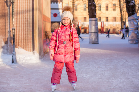 Adorable little girl skating on the ice-rink photo