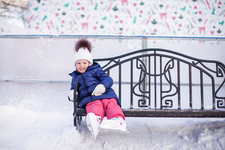 Little girl sitting on a bench in the skating rink photo