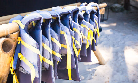 dry life jackets on the white beach photo