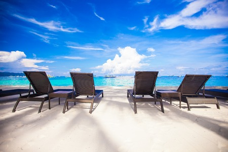 Beach chairs in exotic resort on perfect white sandy beach photo