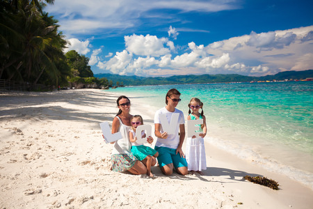 Young happy family of four on tropical vacation with word LOVE photo
