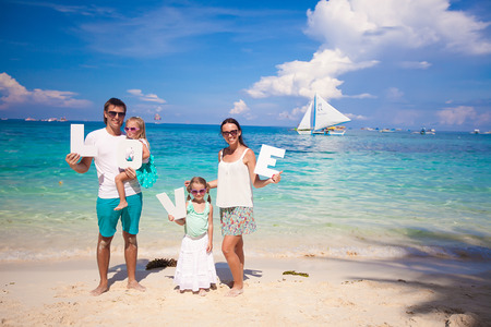 Young happy family on tropical vacation with word LOVE photo