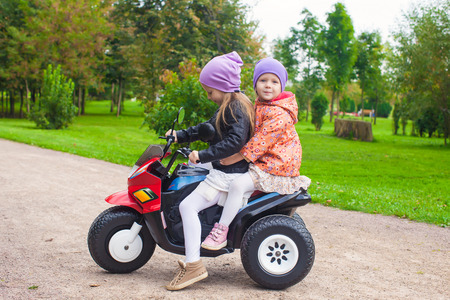 Adorable little girls riding on kids bike in the green park photo