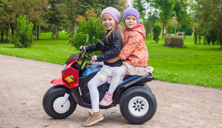 Portrait of adorable little girls ride a motorbike in green park photo