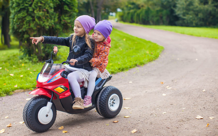Little adorable sisters sitting on toy motorcycle in green park photo