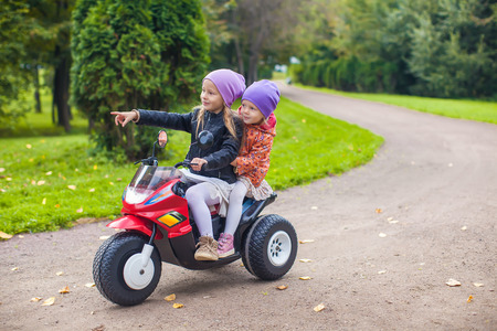 Adorable little girls riding on motobike in the green park photo