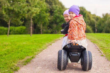 Portrait of little girls ride a motorbike outdoors photo