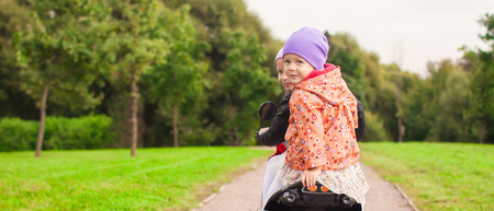 Portrait of little cute girls ride a motorbike outdoors photo
