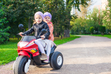 Adorable little girls riding on kids motobike in the green park photo