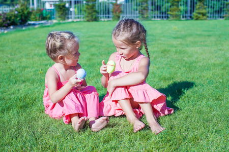 Adorable little girls having fun with Easter Eggs on green grass photo