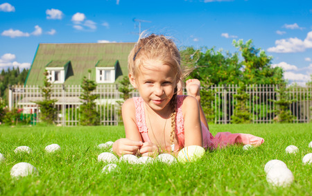 Portrait of little adorable girl playing with white Easter eggs in the yard photo