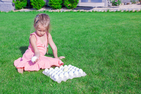 Adorable little girl holding a white Easter egg in her yard photo