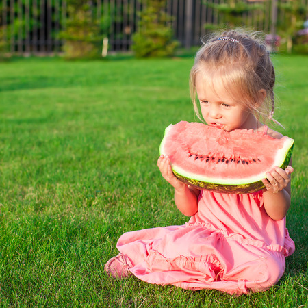 Little girl eating a ripe juicy watermelon in summertime photo