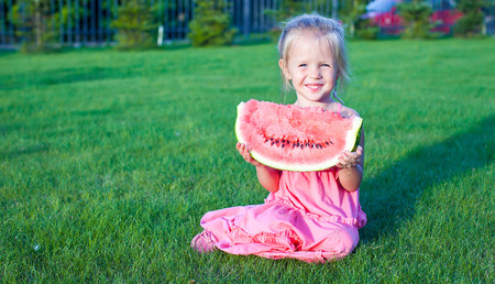 Little adorable funny girl with a piece of watermelon in hands photo