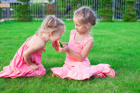 Little adorable girls eating a ripe juicy watermelon in summertime photo