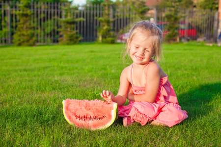 Little smiling girl with a piece of watermelon in hands photo