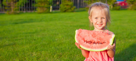 Little girl with big piece of watermelon in hands on green grass photo