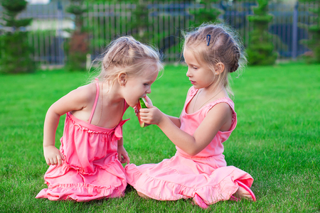 Older sister feeding younger piece of watermelon on a hot summer day photo