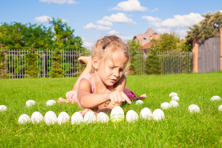 Portrait of little adorable girl playing with white Easter eggs on green grass photo