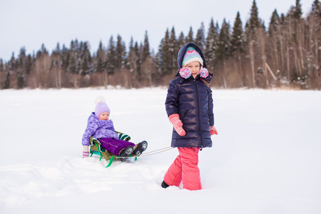 Adorable happy girl sledding her little sister photo