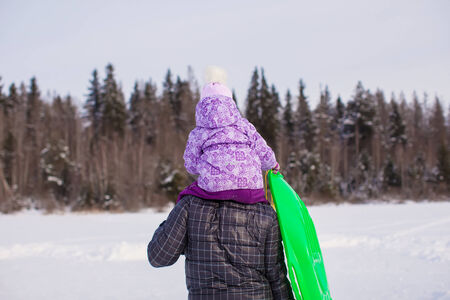 Little girl riding on young dad outdoors in cold winter day photo
