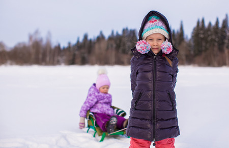 Adorable little happy girl sledding her sister photo
