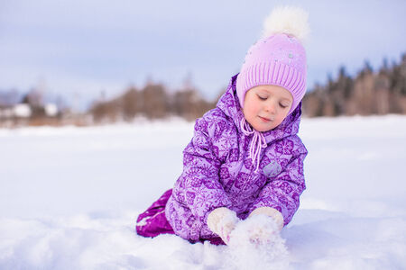 Happy little girl playing with snow at winter sunny day photo