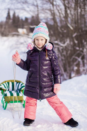Little girl goes sledding on a warm winter day photo