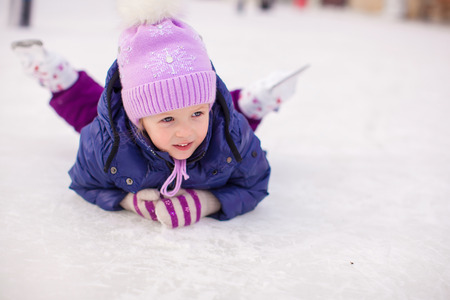 ice rink: Adorable little girl sitting on ice with skates after the fall