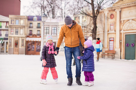 Little girls with young father enjoying skating photo