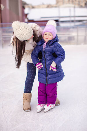 iceskating: Happy adorable little girl and young mother learning ice-skating Stock Photo