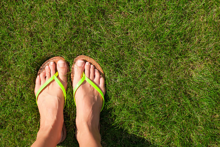 Closeup of bright flip flops and legs on green grass photo