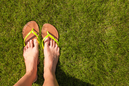 informal clothes: Closeup of womans legs in slippers on green grass Stock Photo